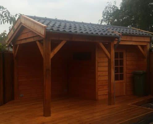 Houten tuinhuis met veranda en zwarte dakpannen