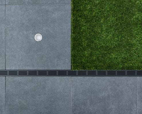 Tuinproject aan de Berkelstraat in Almere. Wij hebben hier grote tegels met kunstgras aangelegd. Je ziet een detailfoto van de legging