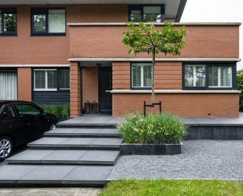 Luie trap van grote grijze tegels gecombineerd met grind en een stenen bloembak