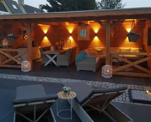 Een terrasoverkapping van Snijers Tuinen. Deze overkapping is gefotografeerd in de avond zodat je de fraaie verlichting kunt zien.